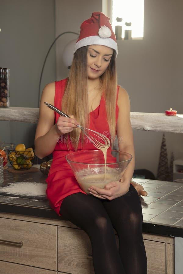 圣诞节衣物的俏丽的女孩坐桌和蛋糕为焙烤食品做准备 免版税图库摄影