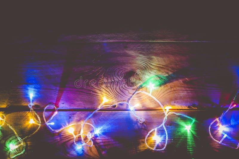 圣诞节装饰光 圣诞节在木头的诗歌选光 在土气棕色板条的五颜六色的Xmas电灯泡 免版税库存照片