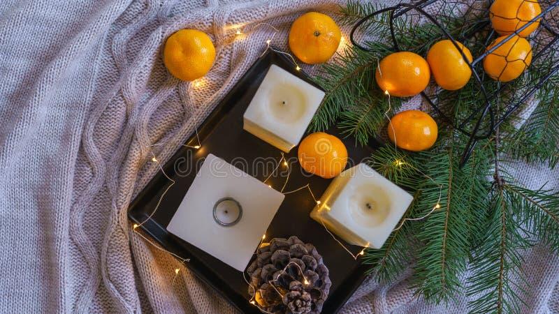 圣诞节装饰启发静物画装饰橙色蜜桔,杉木在黑盘子舒适彩色小灯的锥体蜡烛在灰色 图库摄影