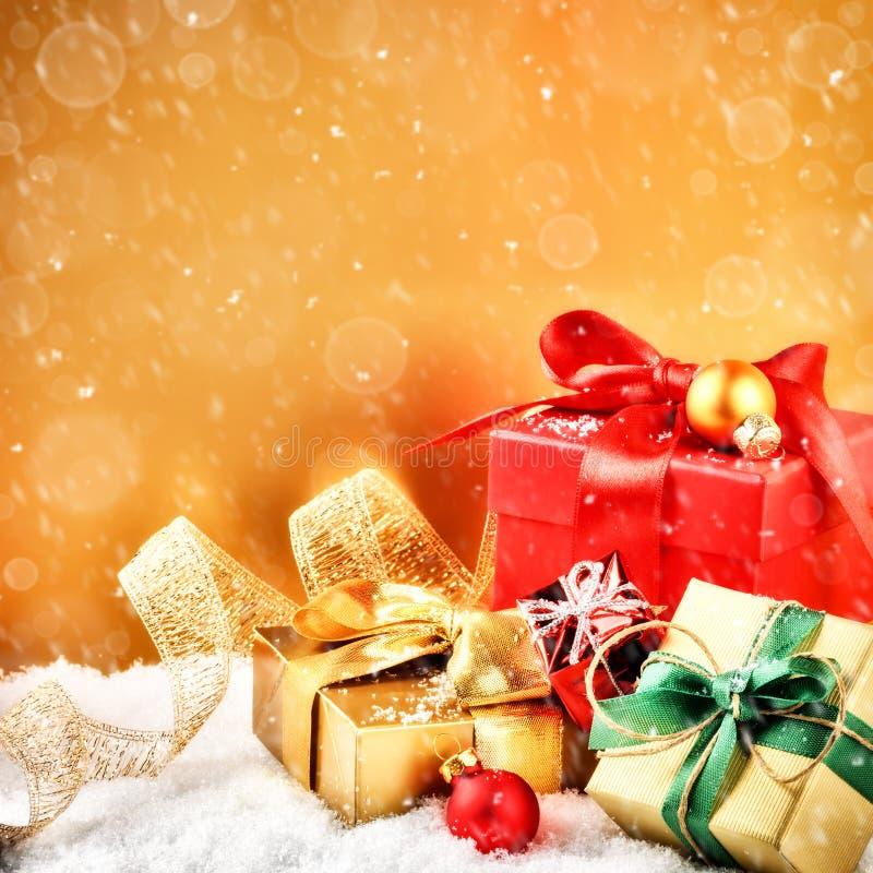 圣诞节装饰品和礼物在金黄和红色口气 图库摄影