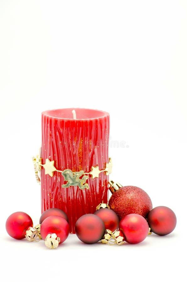圣诞节装饰品-红色蜡烛和红色和金装饰品 免版税库存照片