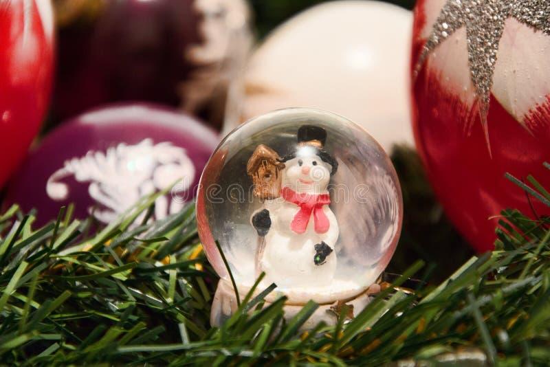 圣诞节装饰生态学木 与雪人的发光的不可思议的水晶球和在树枝杈的圣诞节球 降雪的圆顶有xmas背景 免版税库存图片
