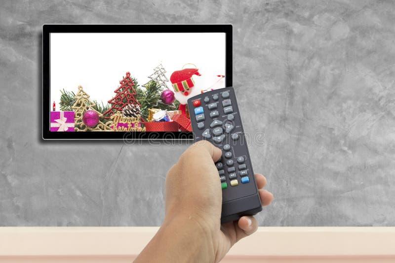 圣诞节装饰用手对负遥控在有混凝土墙的电视屏幕背景的 免版税库存图片