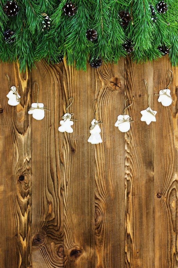 圣诞节装饰用曲奇饼,杉树在与copyspace的黑暗的木背景分支 免版税库存照片