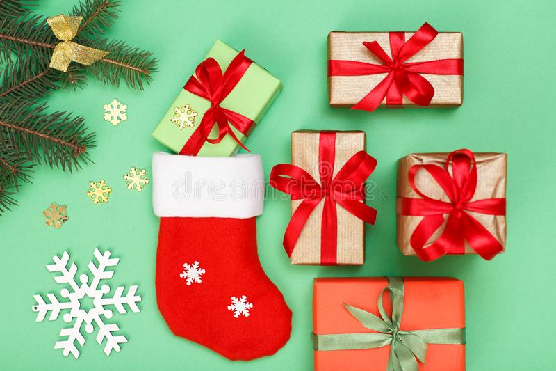 圣诞节装饰装饰新家庭想法 圣诞老人的起动、礼物盒、杉树分支与锥体和装饰snowflackes在绿色背景 顶层 免版税库存图片