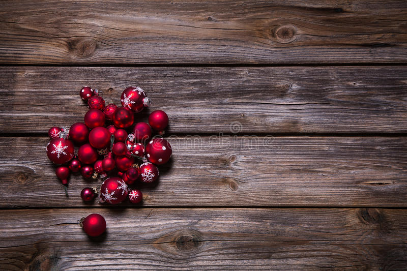 圣诞节装饰:在老木土气背景的红色球 库存图片