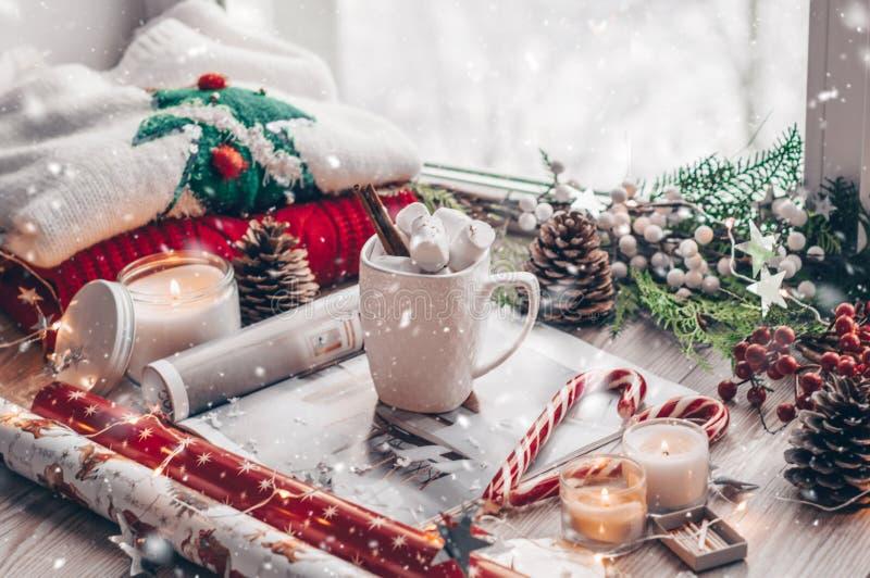 圣诞节装饰:温暖的毛线衣、杯子热的可可粉用蛋白软糖,糖果、蜡烛和圣诞树 冬天心情,装饰 库存照片