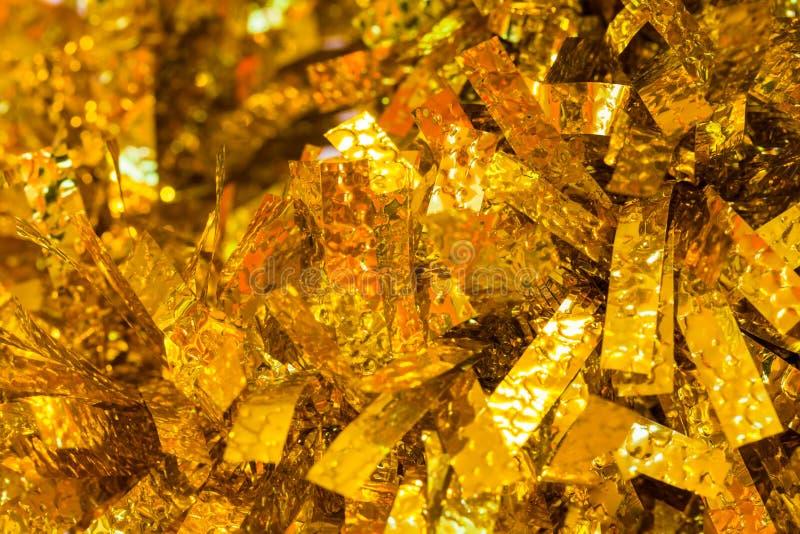 圣诞节装饰-金子和黄色圣诞节闪亮金属片是作为圣诞灯摘要背景 免版税库存图片