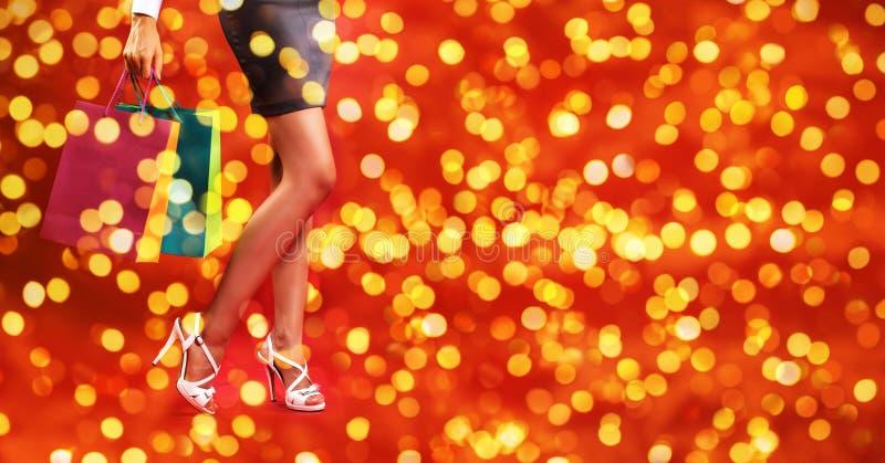 圣诞节购物、腿妇女有鞋子的和袋子在被弄脏的增殖比 免版税库存照片