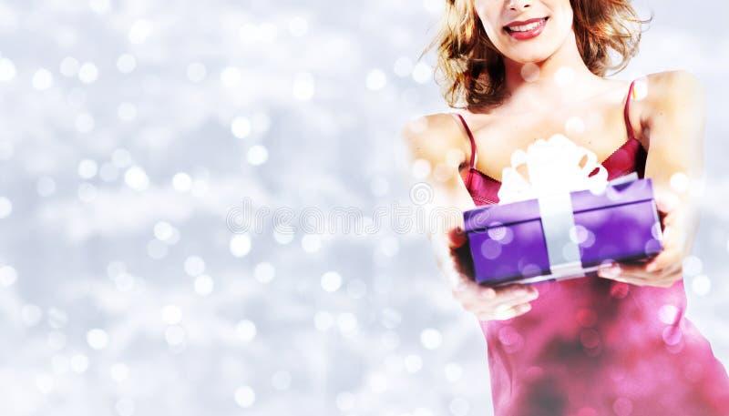 圣诞节购物,有礼物包裹的微笑的妇女在被弄脏的b 库存照片