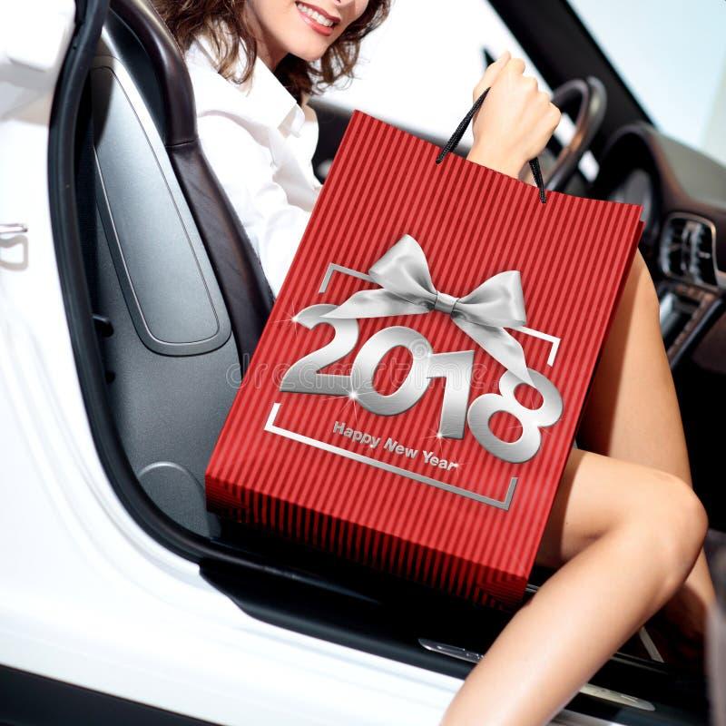 圣诞节购物,有袋子的微笑的妇女在汽车和ha得到 免版税库存照片