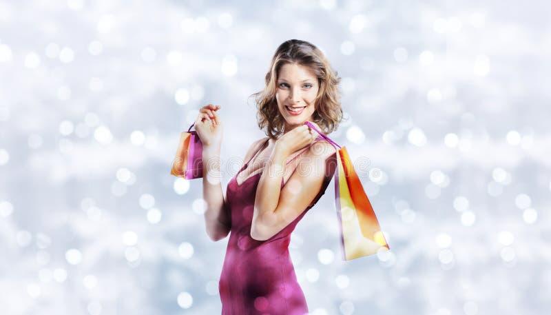圣诞节购物,有袋子的微笑的妇女在被弄脏的明亮的锂 免版税库存图片