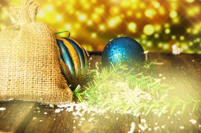 圣诞节金发光的背景,圣诞节与礼物,球,在老黑暗的委员会的闪亮金属片,新年的帆布袋子2019年 免版税图库摄影