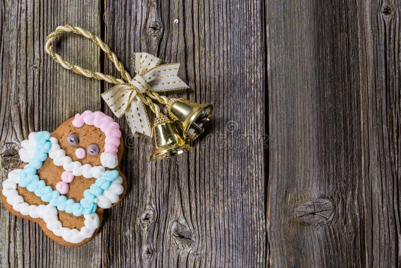 圣诞节铃声和在木板材的姜饼曲奇饼 免版税库存图片