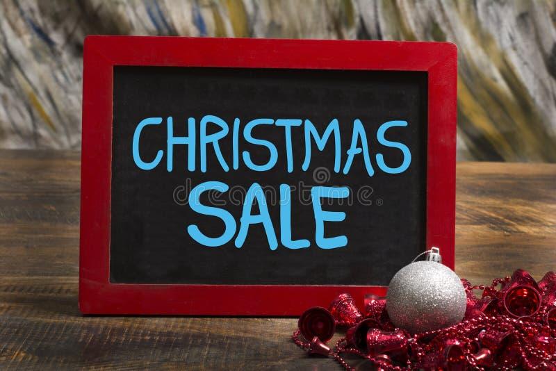 圣诞节销售在桌上的木制框架黑板与球和圆环 免版税图库摄影