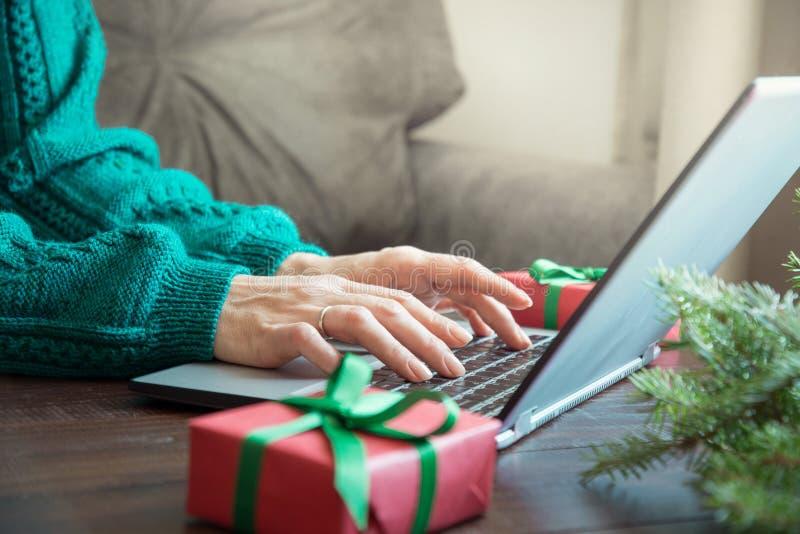 圣诞节销售额 键入在家庭内部的膝上型计算机的妇女 Xmas概念 飞行的假日 库存照片