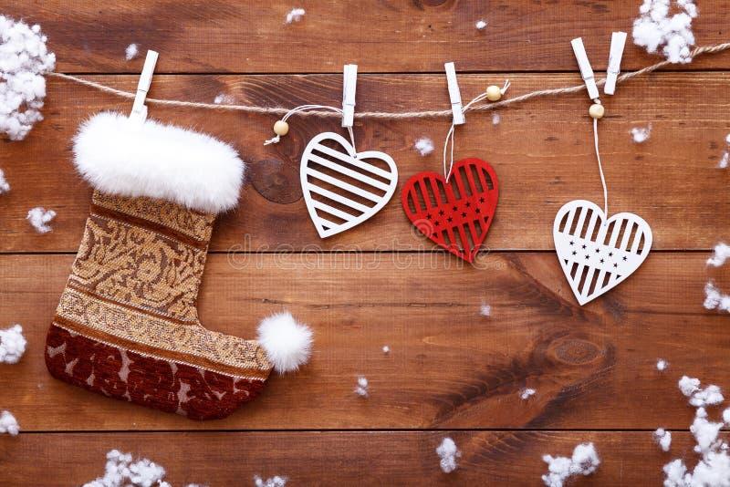 圣诞节长袜,垂悬在棕色木背景, xmas情人节卡片,拷贝空间,顶视图的白色红色心脏 免版税库存图片