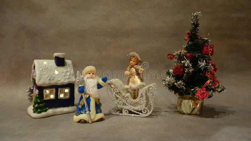 圣诞节静物画、玩具圣诞老人项目和雪少女小提琴手在圣诞树附近 免版税库存照片