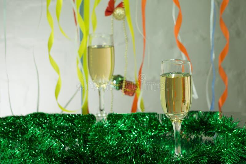 圣诞节静物画-两杯与蓝色Xmas球的在圣诞树背景的汽酒和闪亮金属片 库存照片