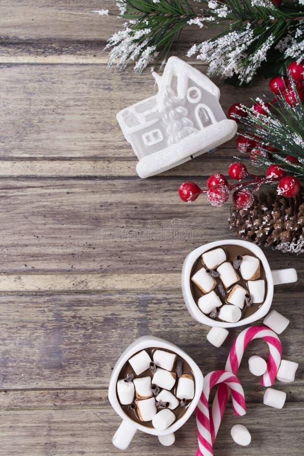 圣诞节静物画-两个杯子热巧克力用蛋白软糖、糖果、玩具冷杉房子和分支用莓果 库存图片