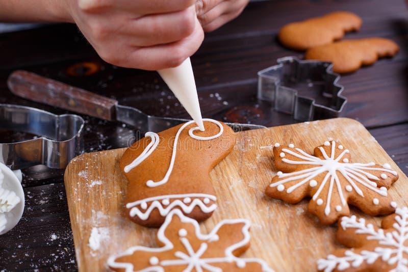 圣诞节面包店的装饰过程 装饰h的妇女手 免版税库存照片