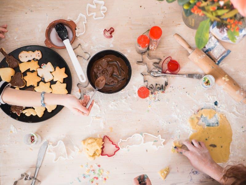 圣诞节面包店:准备圣诞节曲奇饼,与sifferent烘烤的供应的顶视图的女孩 免版税库存照片