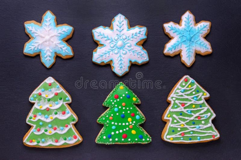 圣诞节食物,手工制造曲奇饼姜饼喜欢圣诞树和雪花在黑背景 免版税库存照片