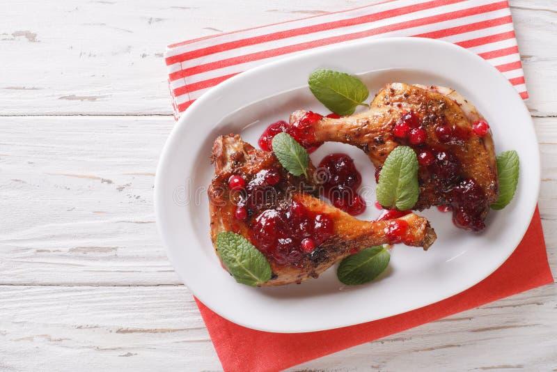 圣诞节食物:有酸果蔓酱和薄菏克洛的被烘烤的鸭子腿 免版税图库摄影