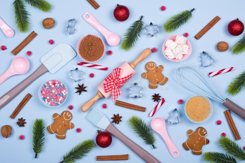 圣诞节香料、曲奇饼切削刀、成份圣诞节烘烤的和厨房用具姜饼曲奇饼在蓝色淡色backgro 库存照片