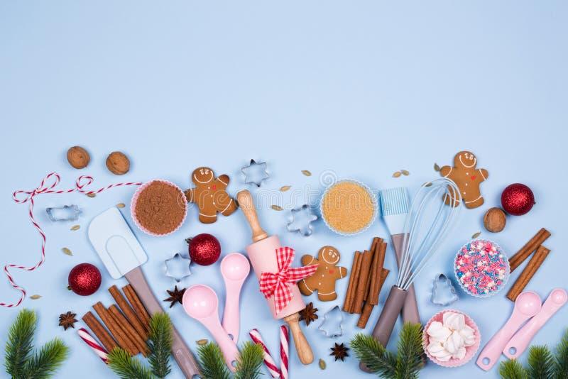 圣诞节香料、曲奇饼切削刀、成份圣诞节烘烤的和厨房用具姜饼曲奇饼在蓝色淡色backgro 库存图片