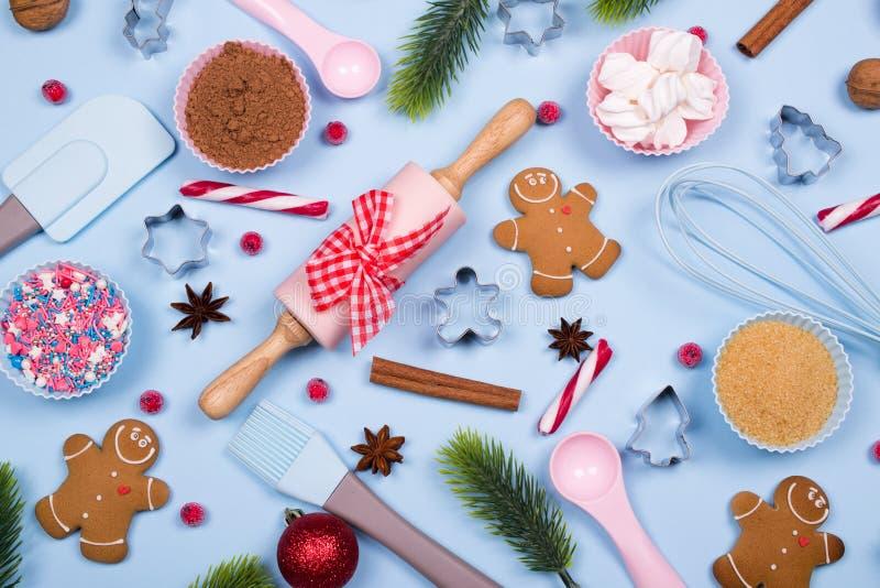 圣诞节香料、曲奇饼切削刀、成份圣诞节烘烤的和厨房用具姜饼曲奇饼在蓝色淡色backgro 图库摄影