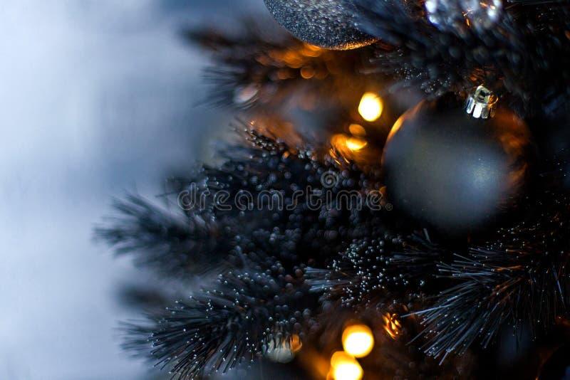 圣诞节黑暗弄脏了与一棵黑圣诞树、装饰品和bokeh光的背景 库存图片