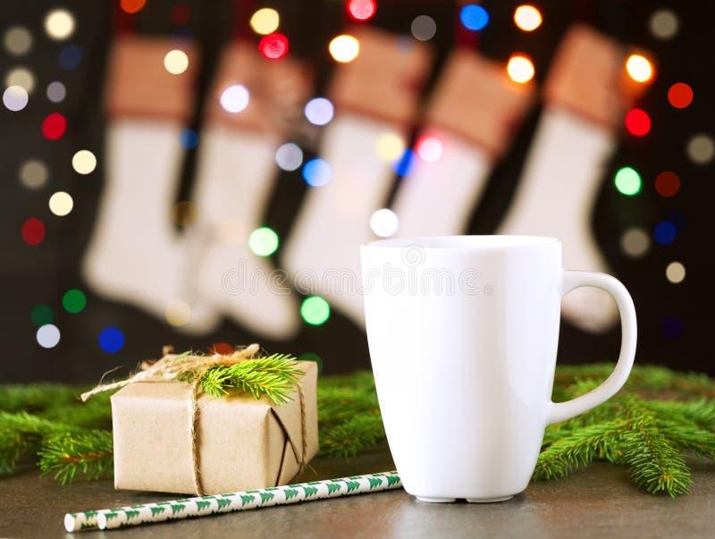 圣诞节黑暗的背景、圣诞节袜子、礼物、冷杉分支、杯子用茶或咖啡,不可思议的bokeh,空的空间 免版税库存照片