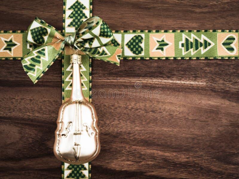圣诞节,在木头,圣诞节装饰,大提琴的礼物丝带 免版税图库摄影