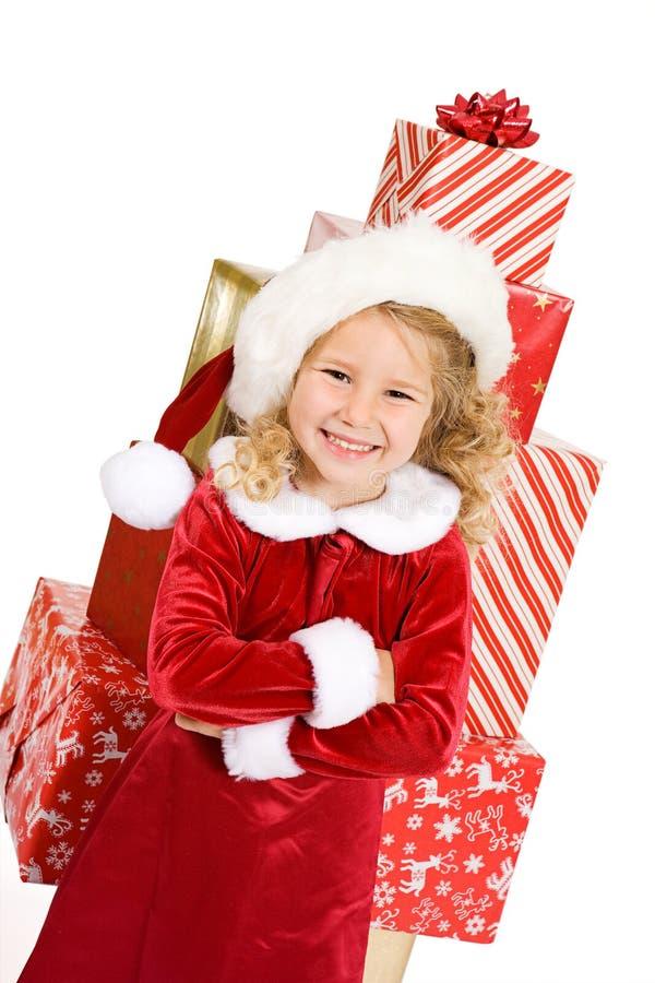 圣诞节:在大堆的女孩被包裹的礼物前面 免版税库存图片