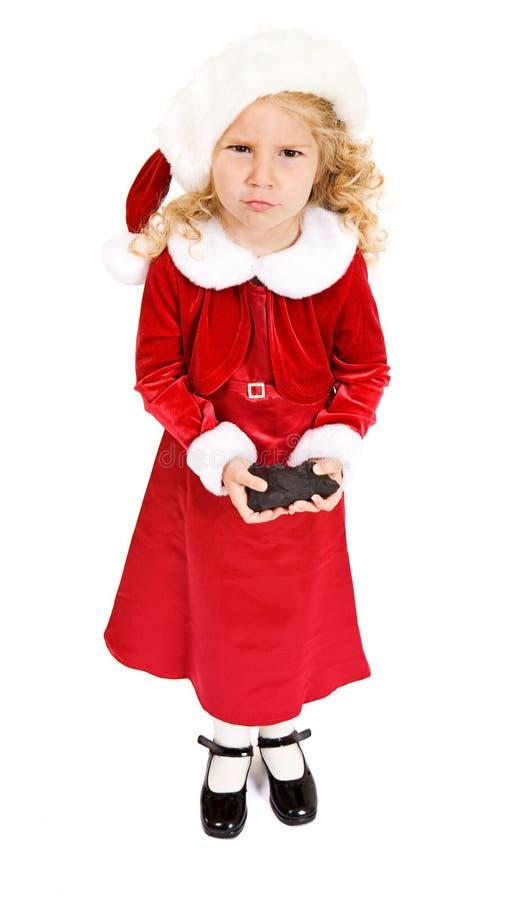 圣诞节:女孩从坏行为的圣诞老人得到煤炭 免版税库存照片