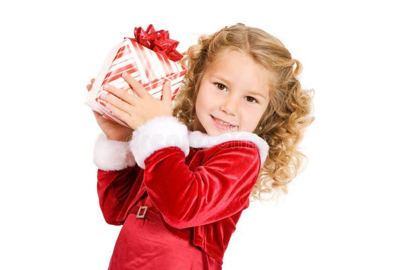 圣诞节:女孩阻止圣诞礼物并且震动猜测W 免版税库存照片
