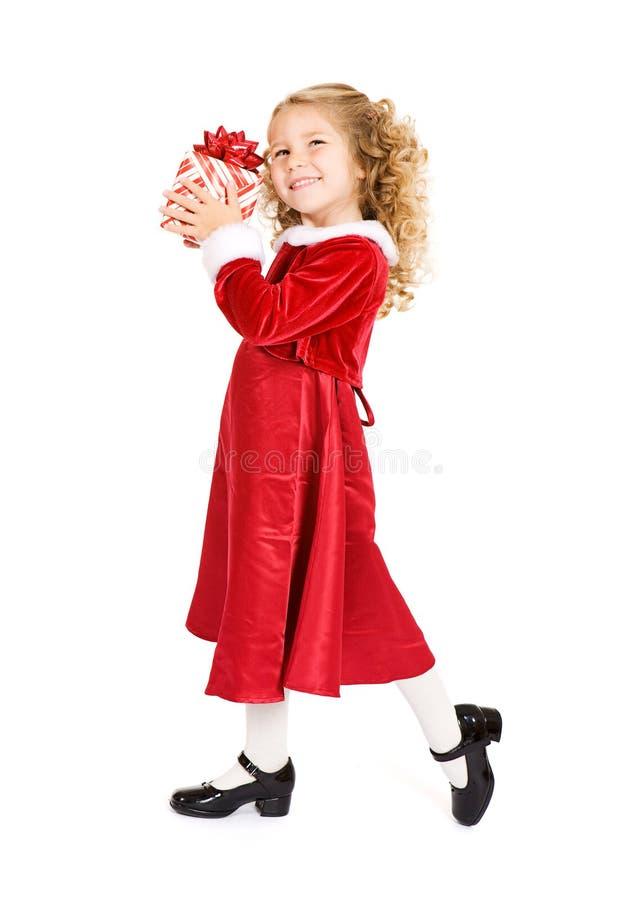 圣诞节:盼望一巨大圣诞礼物的女孩 免版税图库摄影