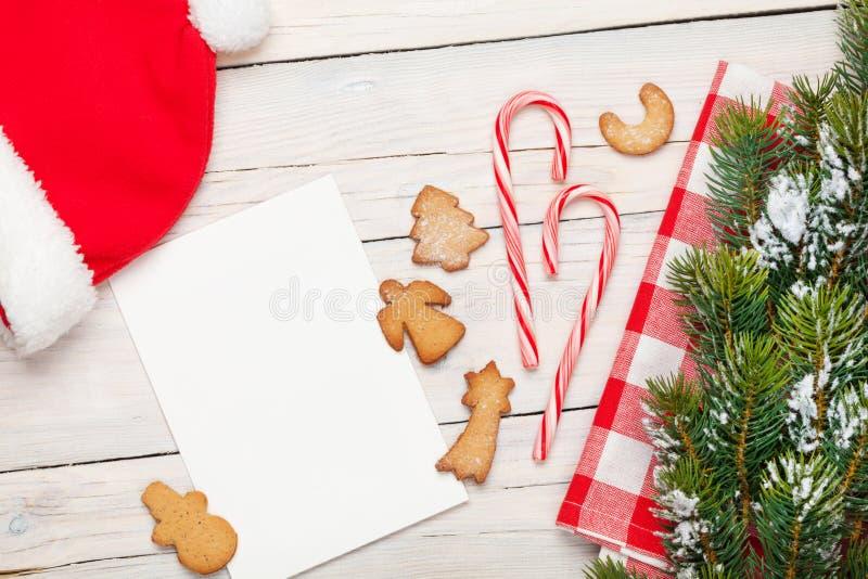 圣诞节贺卡、圣诞老人帽子、姜饼曲奇饼和雪 库存照片