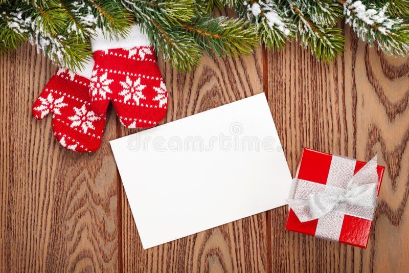 圣诞节贺卡或照片框架和手套在木t 免版税库存图片