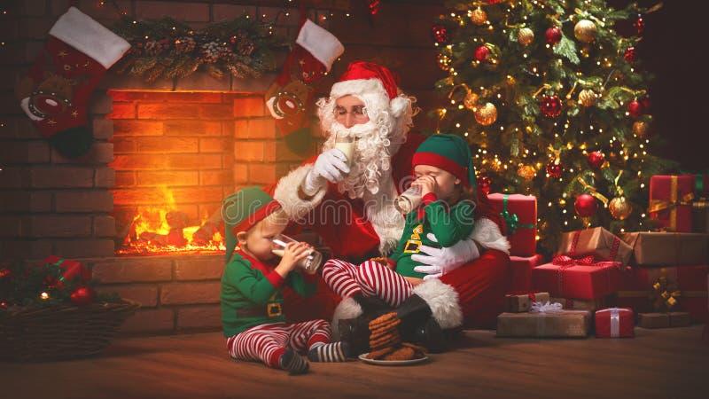 圣诞节 圣诞老人用矮子饮料牛奶和吃曲奇饼 免版税库存图片