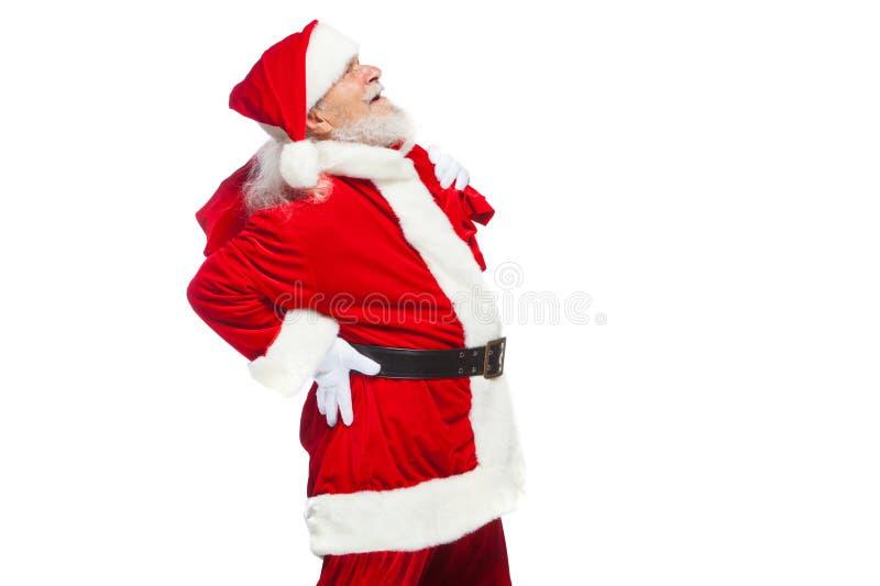 圣诞节 圣诞老人遭受背部疼痛并且拿着与礼物的一个红色袋子在他的 查出在白色 免版税图库摄影