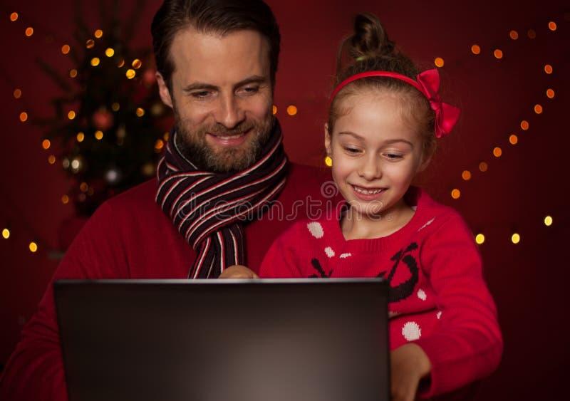 圣诞节-打在便携式计算机上的父亲和女儿比赛 免版税库存照片