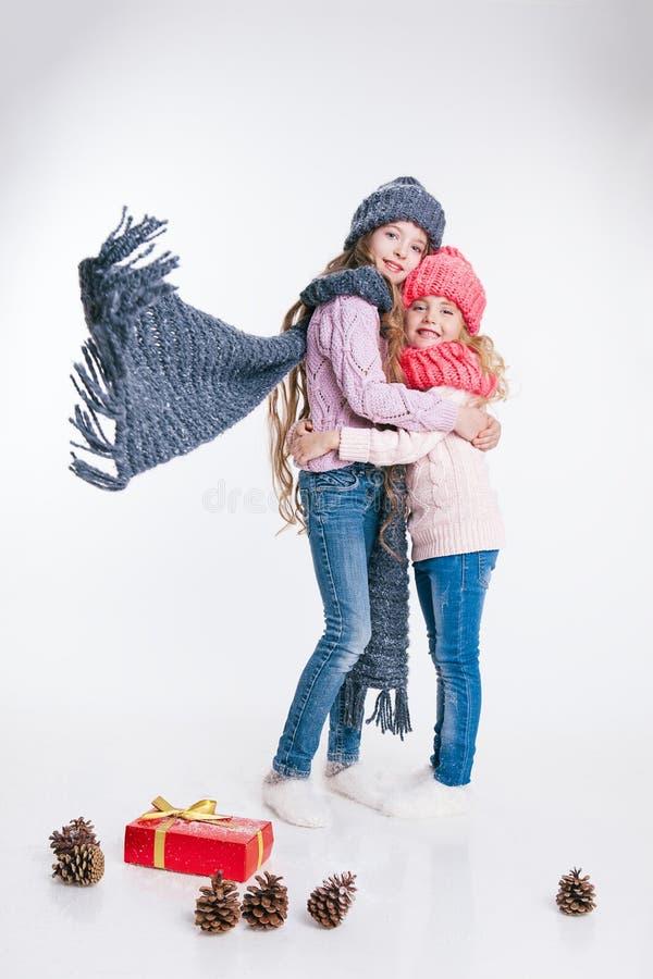 圣诞节 新年度 两个妹对负当前在冬天衣裳 桃红色和灰色帽子和围巾 家庭 冬天 免版税库存照片