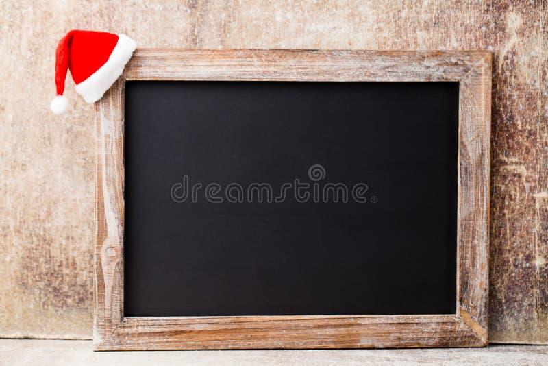圣诞节黑板和装饰在木背景 图库摄影