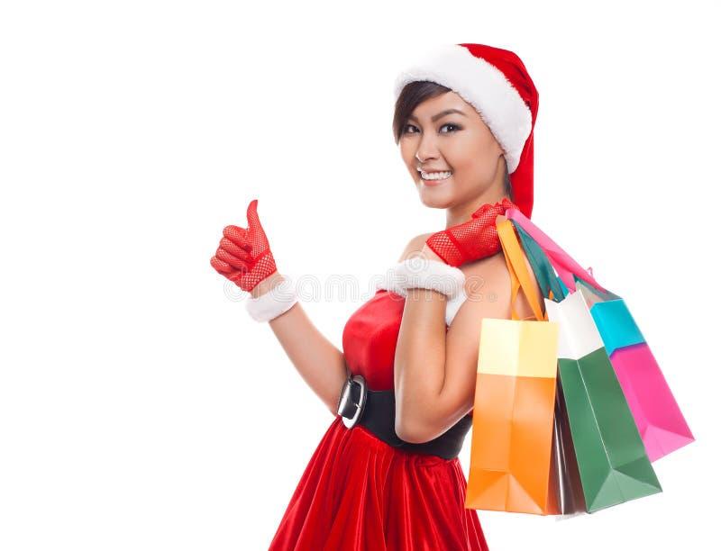 圣诞节购物妇女想法的佩带的圣诞老人帽子和举行 免版税图库摄影