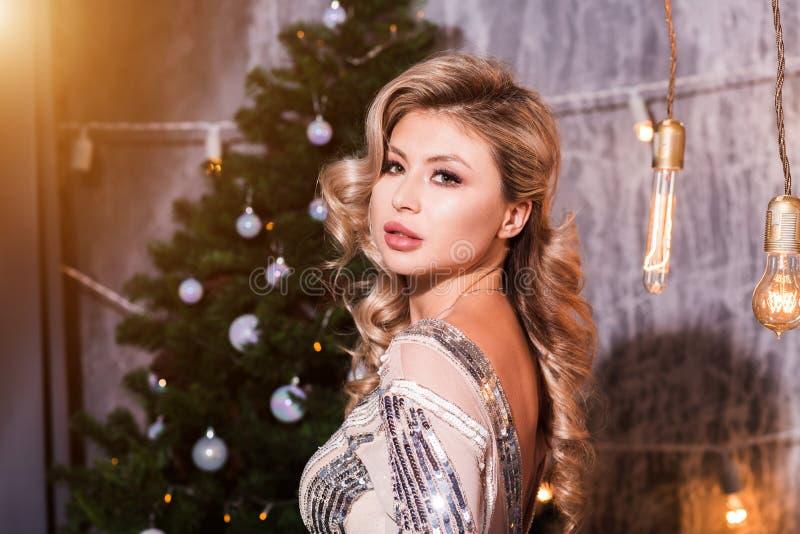 圣诞节 美好的微笑的妇女模型 构成 健康长的发型 礼服的典雅的夫人在圣诞树光 库存图片