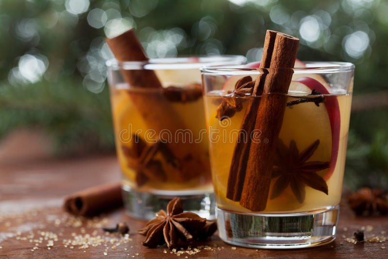 圣诞节仔细考虑了苹果汁用在土气桌,传统饮料上的香料桂香、丁香、茴香和蜂蜜寒假 免版税库存照片