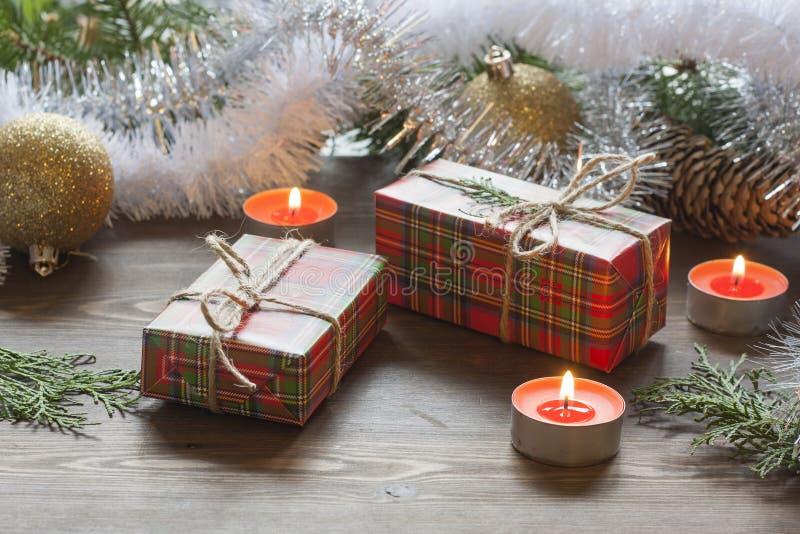 圣诞节giftsChristmas新年装饰中间、果子和闪亮金属片根据灼烧的蜡烛 庆祝的新年 库存照片