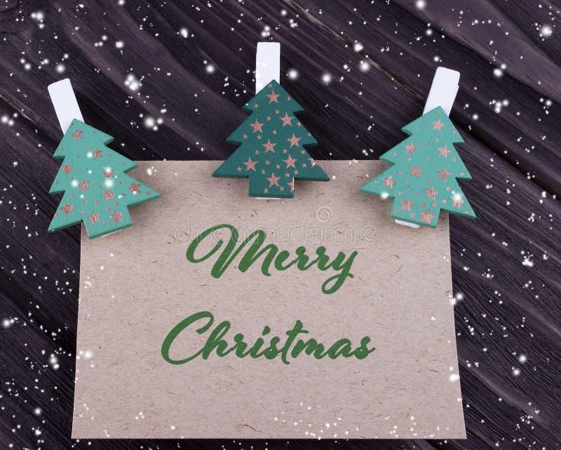 圣诞节Xmas与圣诞树的贺卡在黑暗的木背景的晒衣夹 库存照片